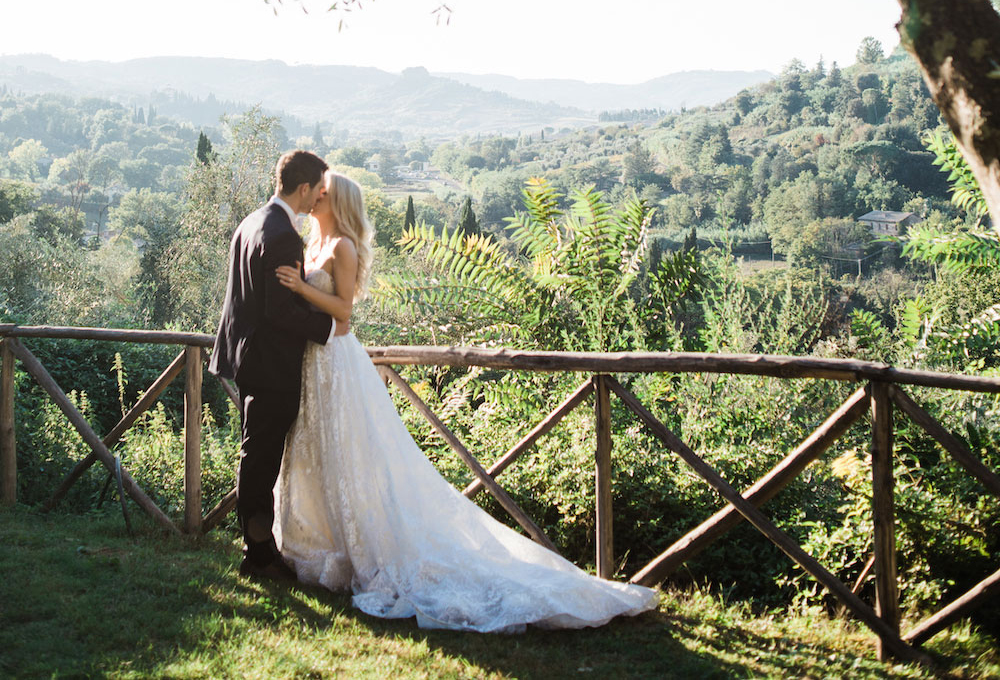 bride with long train  kissing groom in suit with backdrop of sweeping views of green hills