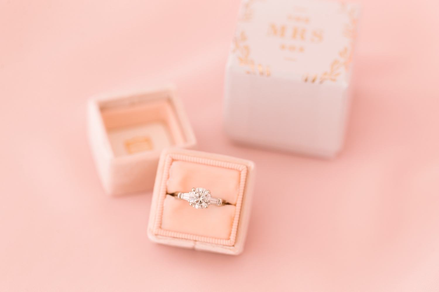 round diamond engagement ring with baguette side stones displayed in blush velvet mrs. box