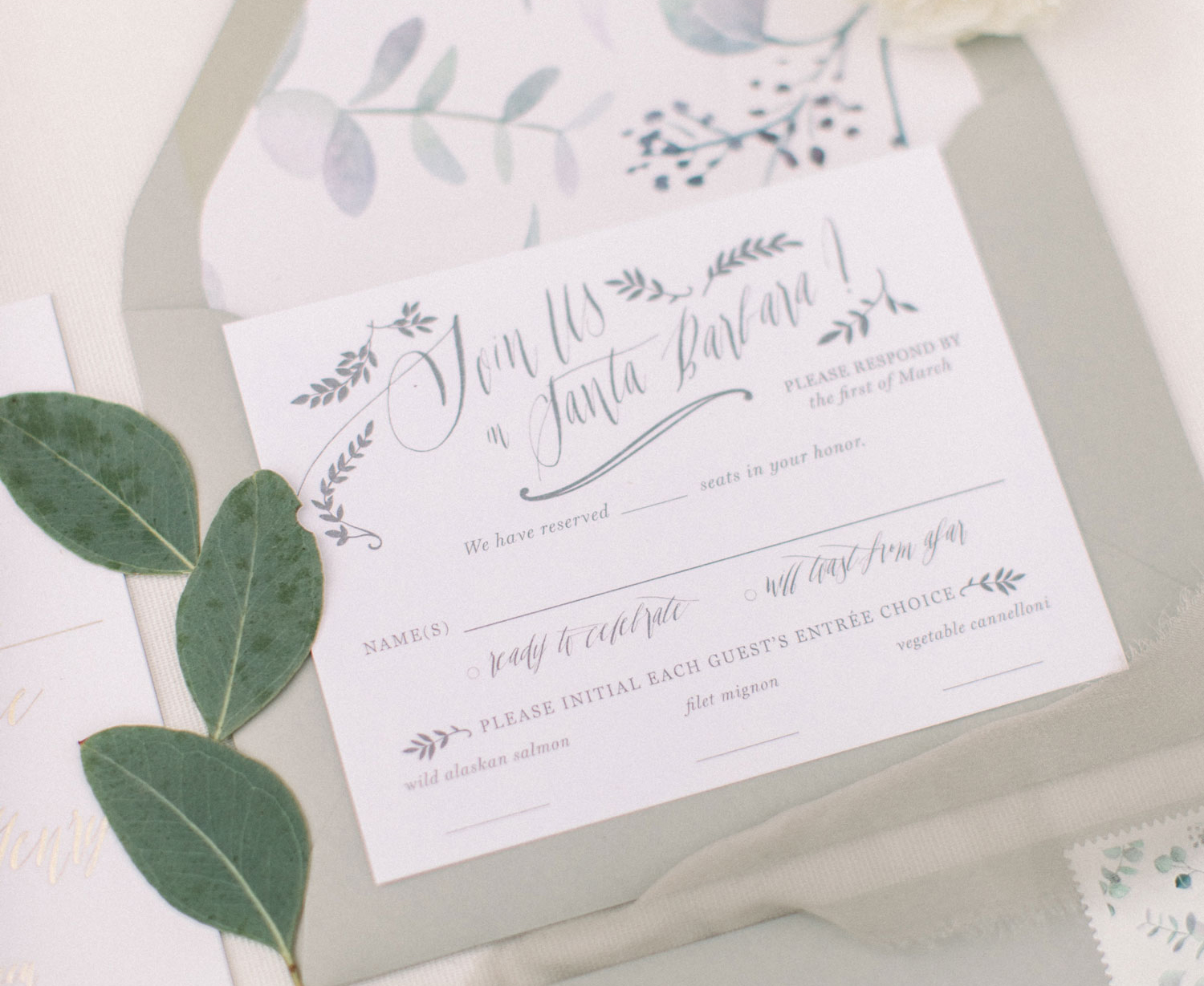 grey-hued invitation with watercolor invitation liner with blueish foliage