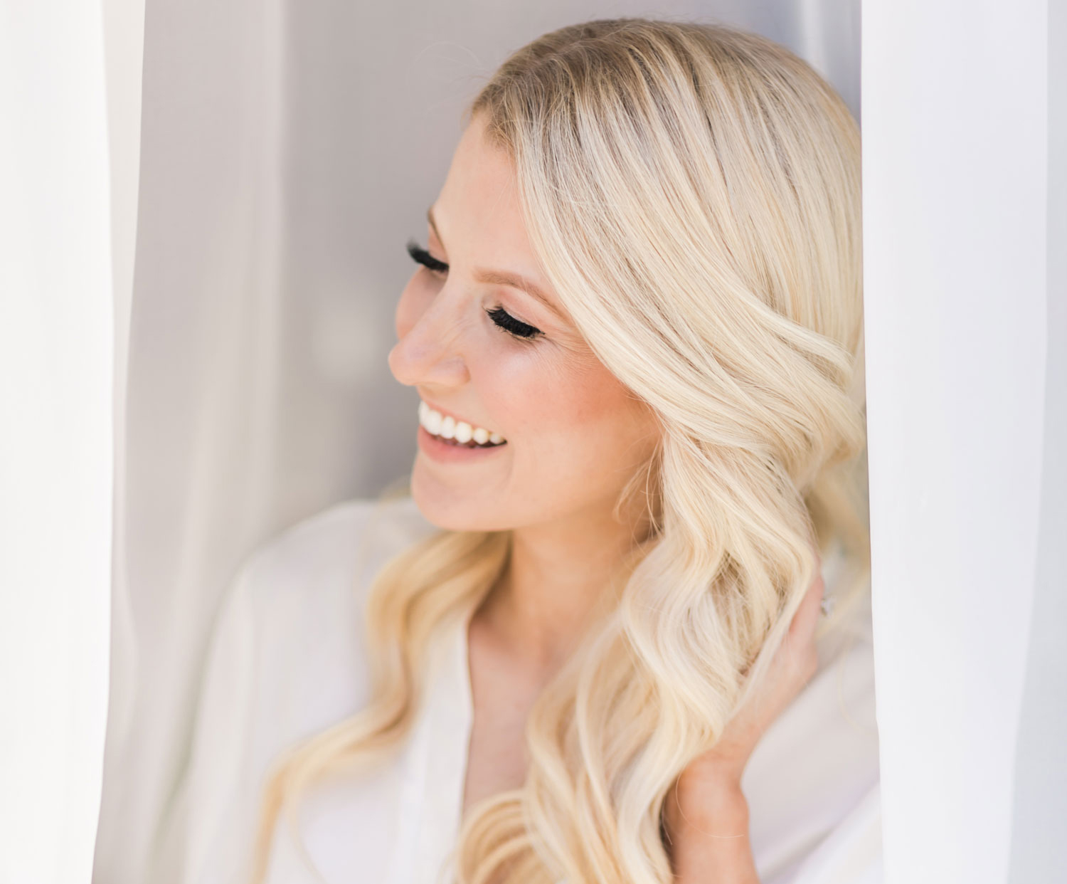 blonde women with soft waves in white robe laughing while looking out window