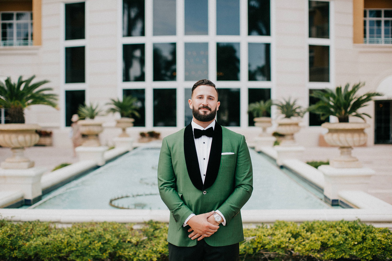 groom in forest green suit jacket standing in front of fountain