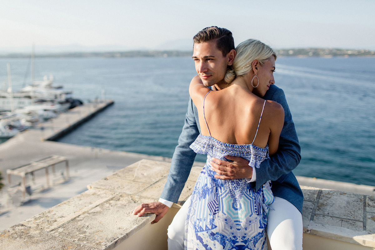 blonde woman in blue patterned dress hugging man in blue linen sports coat in front of ocean