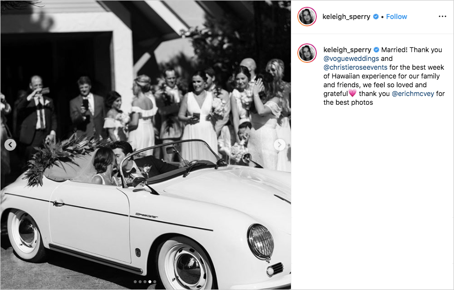 black and white photo of miles teller and keleigh sperry kissing in vintage white convertible outside of wedding