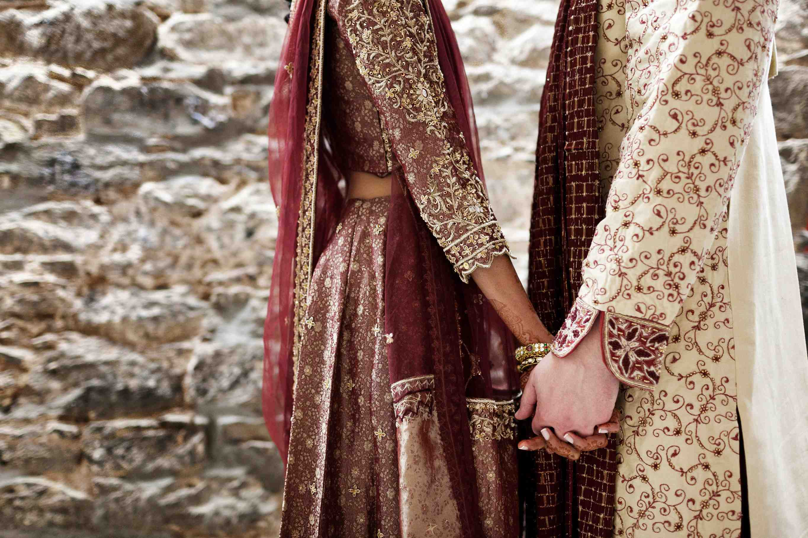 close-up shot of south asian bride in sari holding hands with caucasian groom in south asian wedding attire