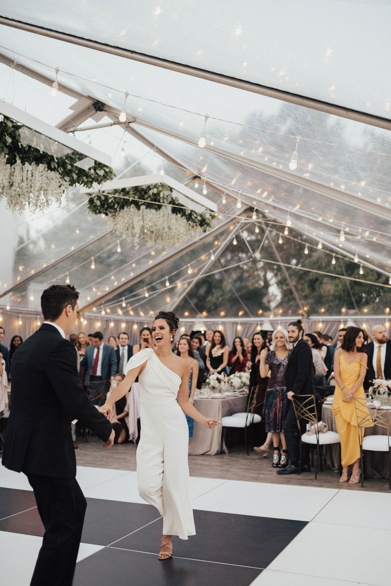 bride in cool white jumpsuit dancing with groom at wedding reception tent wedding first dance