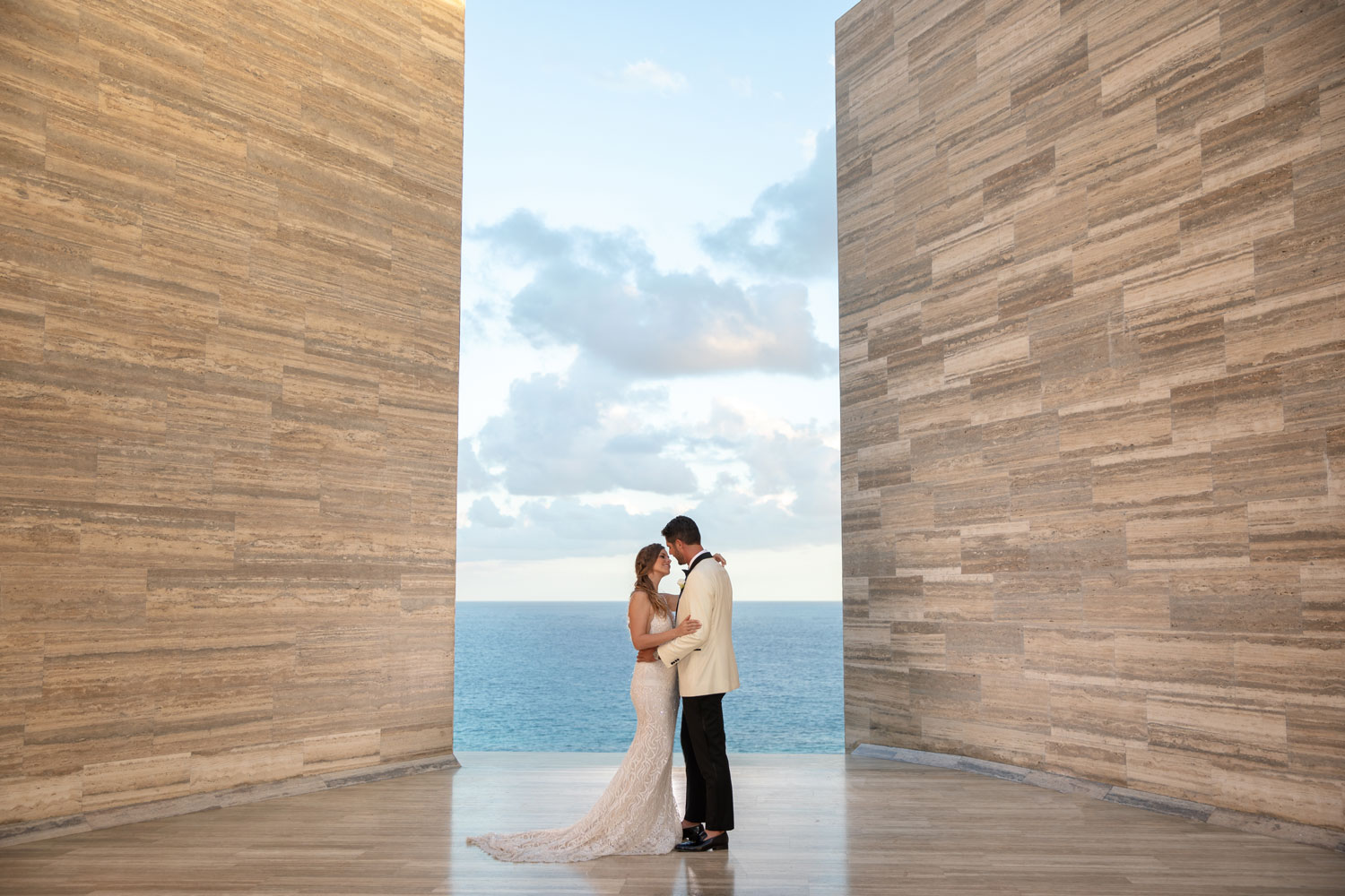 bride and groom between two vast walls with opening overlooking ocean