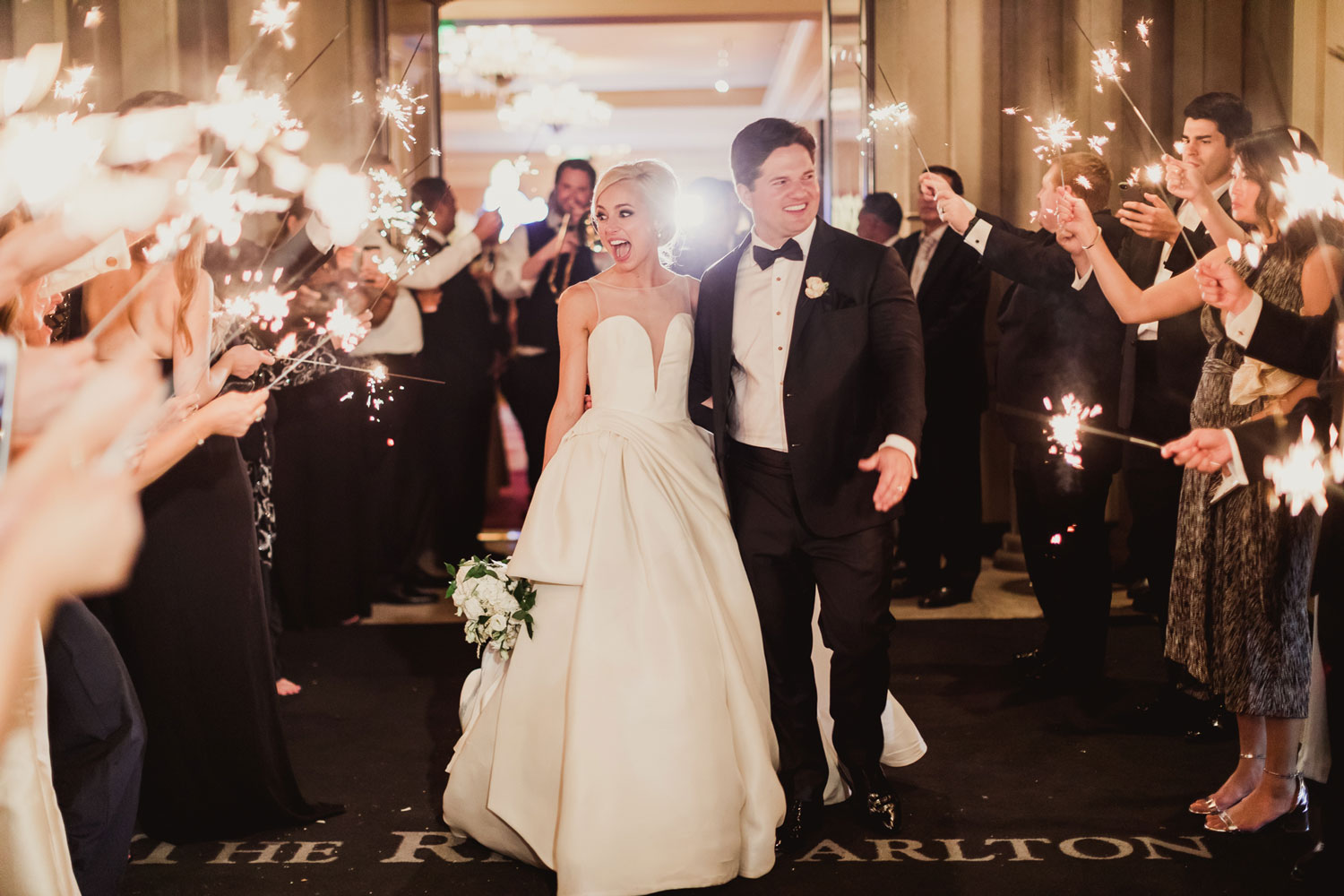 happy newlyweds during sparkler grand exit, bride in ball gown with her jaw dropped