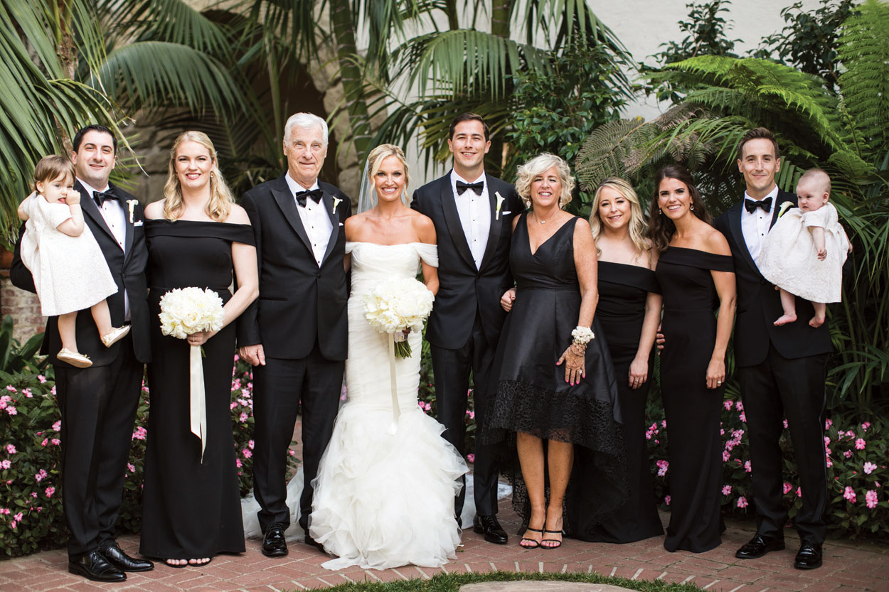formal wedding with family portrait, groomsmen in tuxedos, bridesmaids in black off-the-shoulder dresses