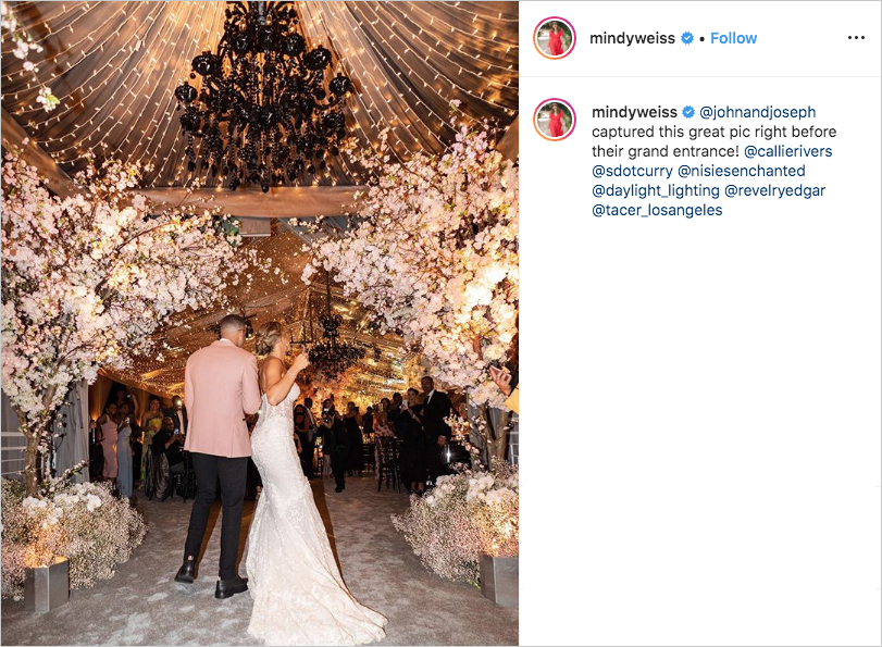 Seth Curry and Callie Rivers entering wedding reception with black chandeliers above