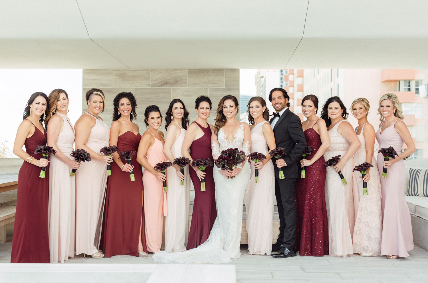 bride with bridesmaids in blush and burgundy and bridesman in suit with bouquet