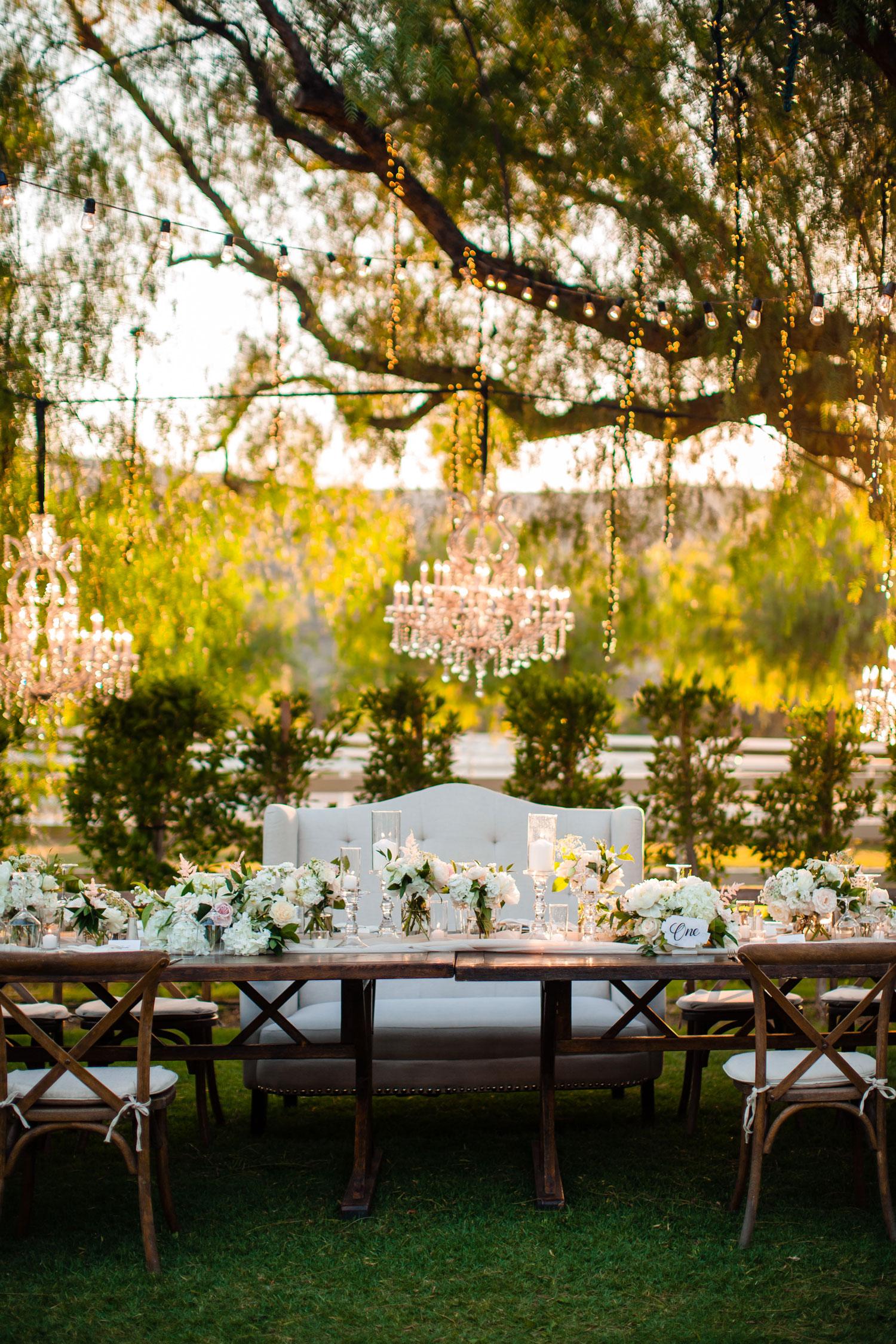 wedding reception outside twinkle lights vineyard wood chairs sweetheart head table settee tessa lyn events