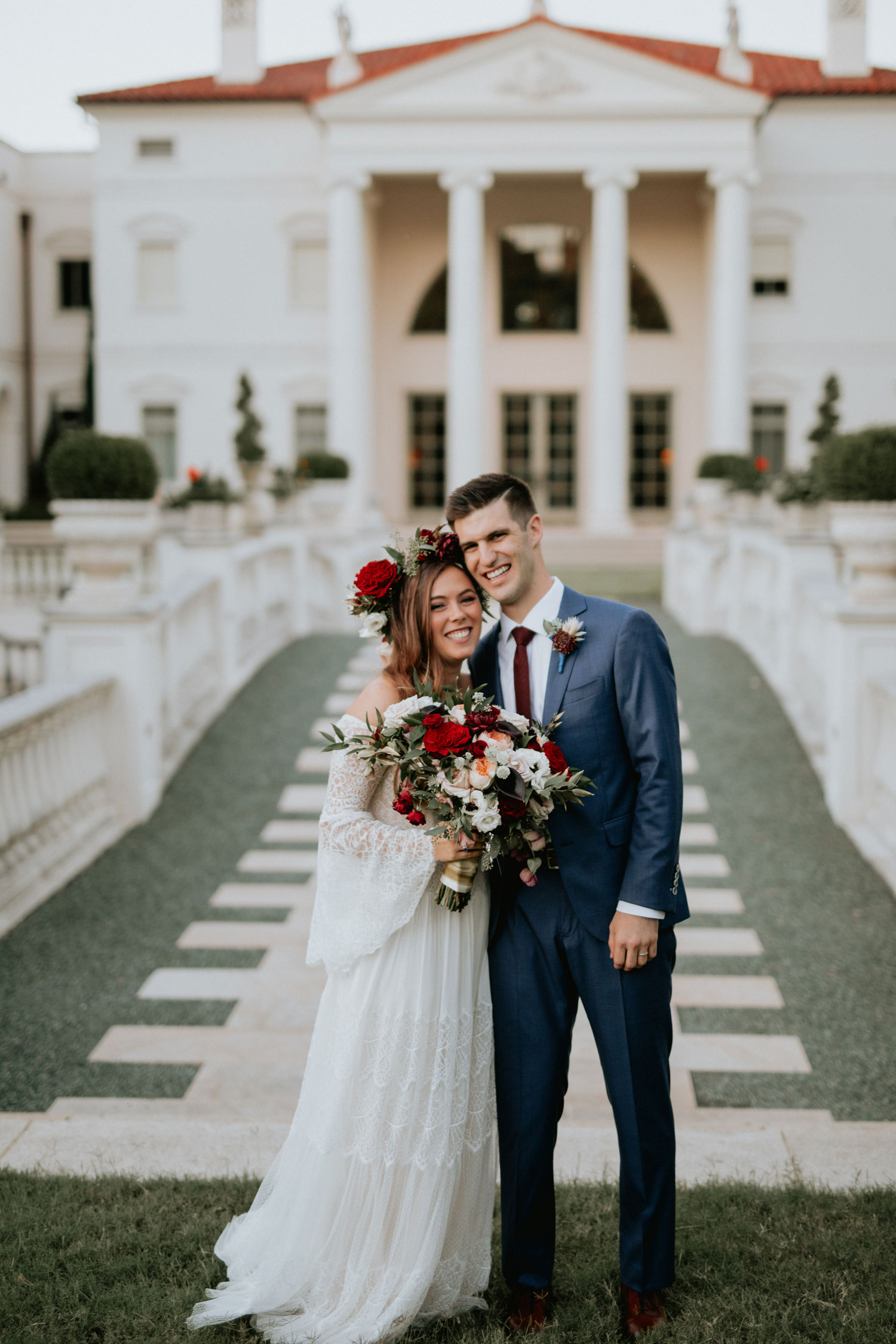 bride and groom outside venue fall wedding flower crown and bouquet burgundy autumn color palette