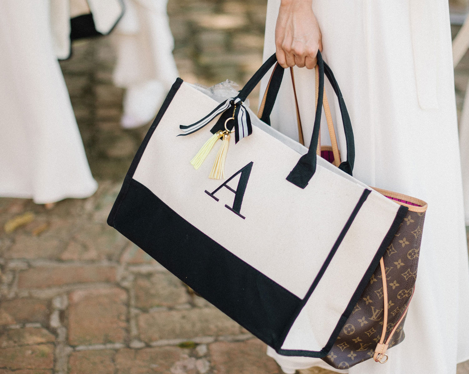 """monogrammed tote with """"A"""" and louis vuitton tote carried by woman in white dress"""
