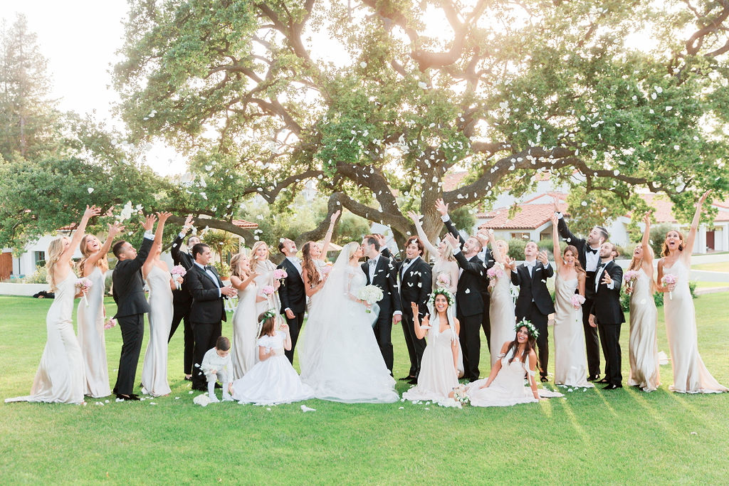 bride and groom kissing while bridal party tosses rose petals at them, bridesmaids in champagne dresses, groomsmen in tuxes
