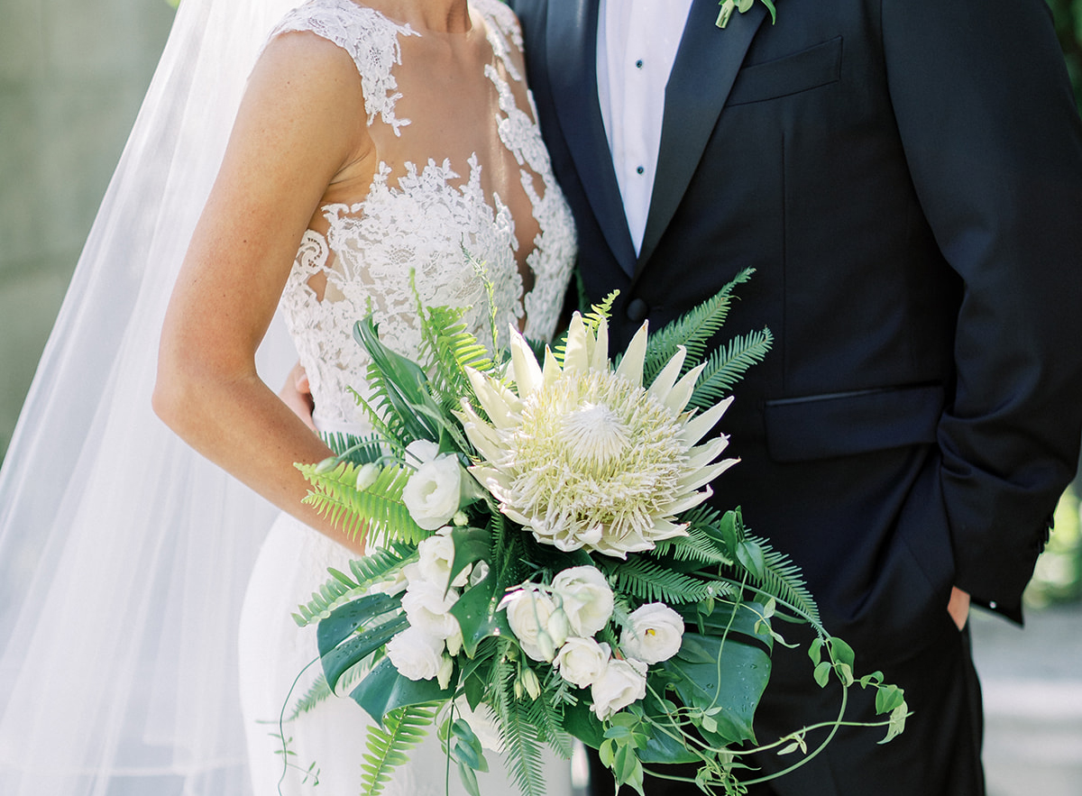 torso of bride and groom, trendy bridal bouquet with large protea bloom, why to have a prenup