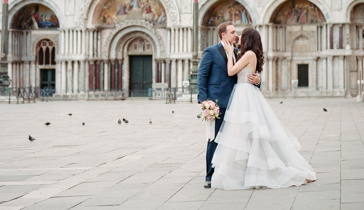 bride and groom kissing in italian plaza during elopement