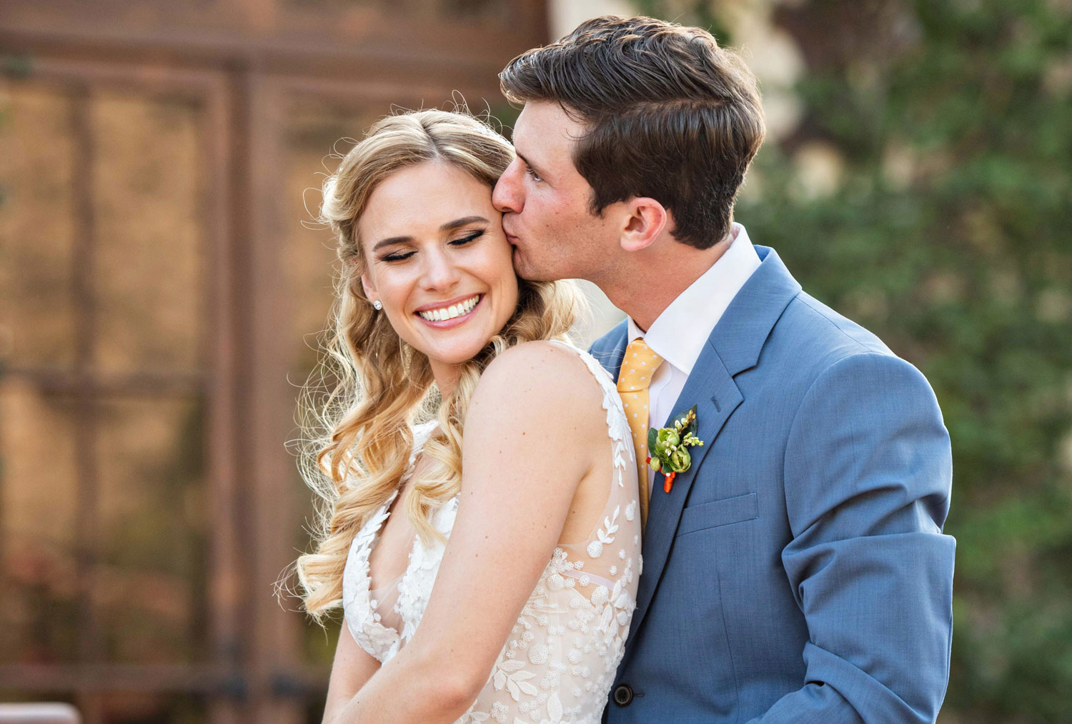 groom kissing bride on the cheek as she grins, what couples forget on their wedding