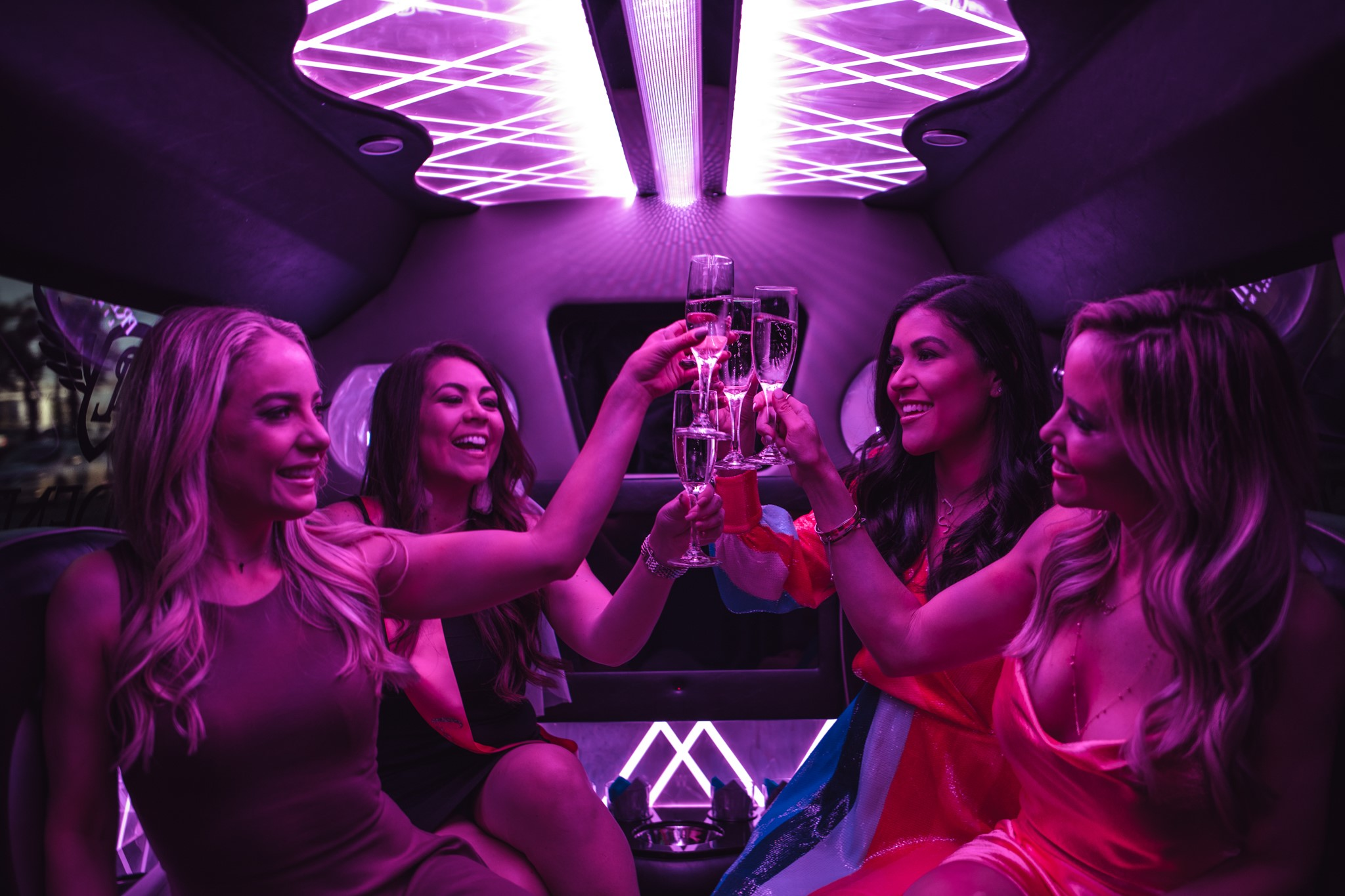 women at bachelorette party toasting champagne in the back of a limo with purple lighting