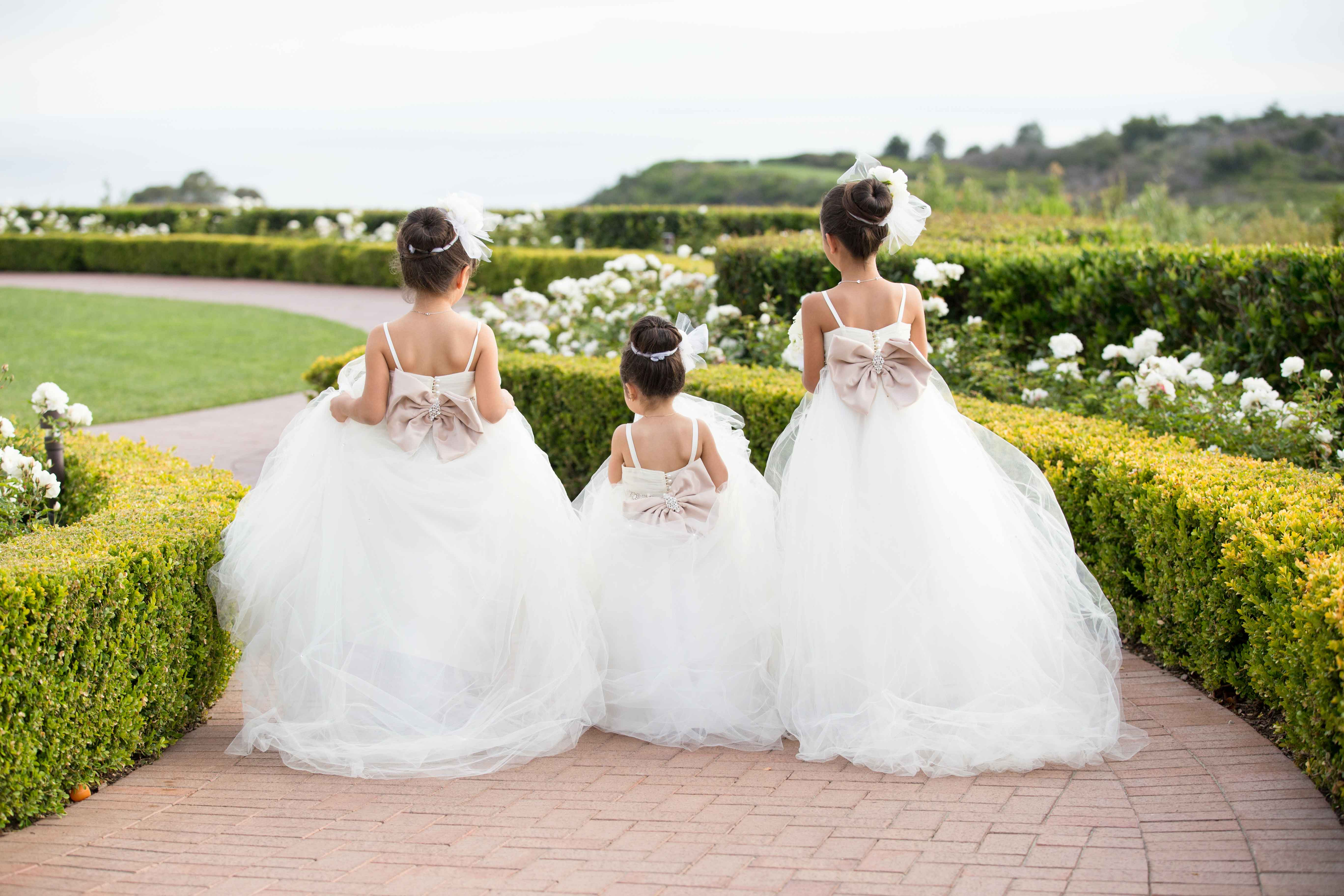 back view of three flower girls in full tulle ballgowns with a taupe bow with rhinestones, sock bun with bow