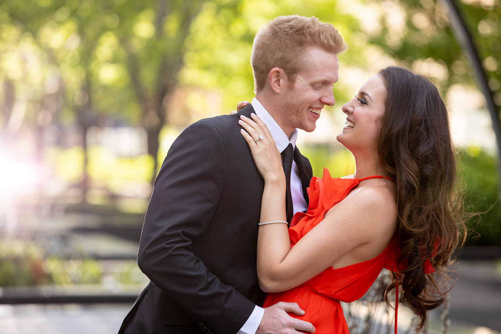 couple posing for their engagement photos, woman in red dress, man in pinstriped suit