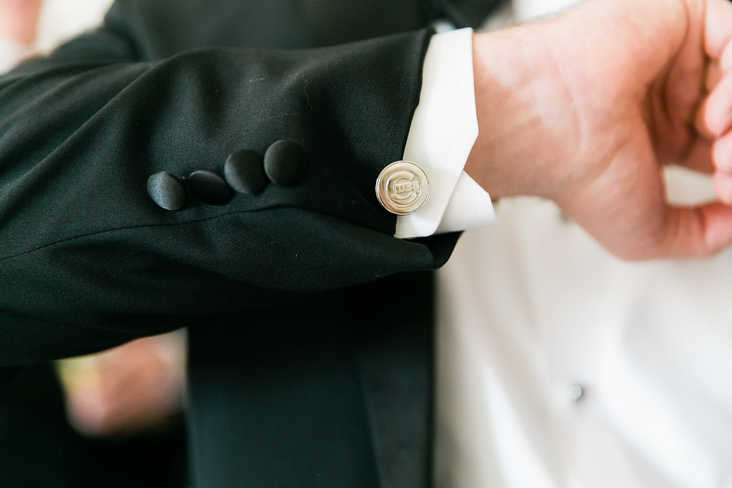 close up of groom adjusting silver cufflinks with logo of the chicago cubs