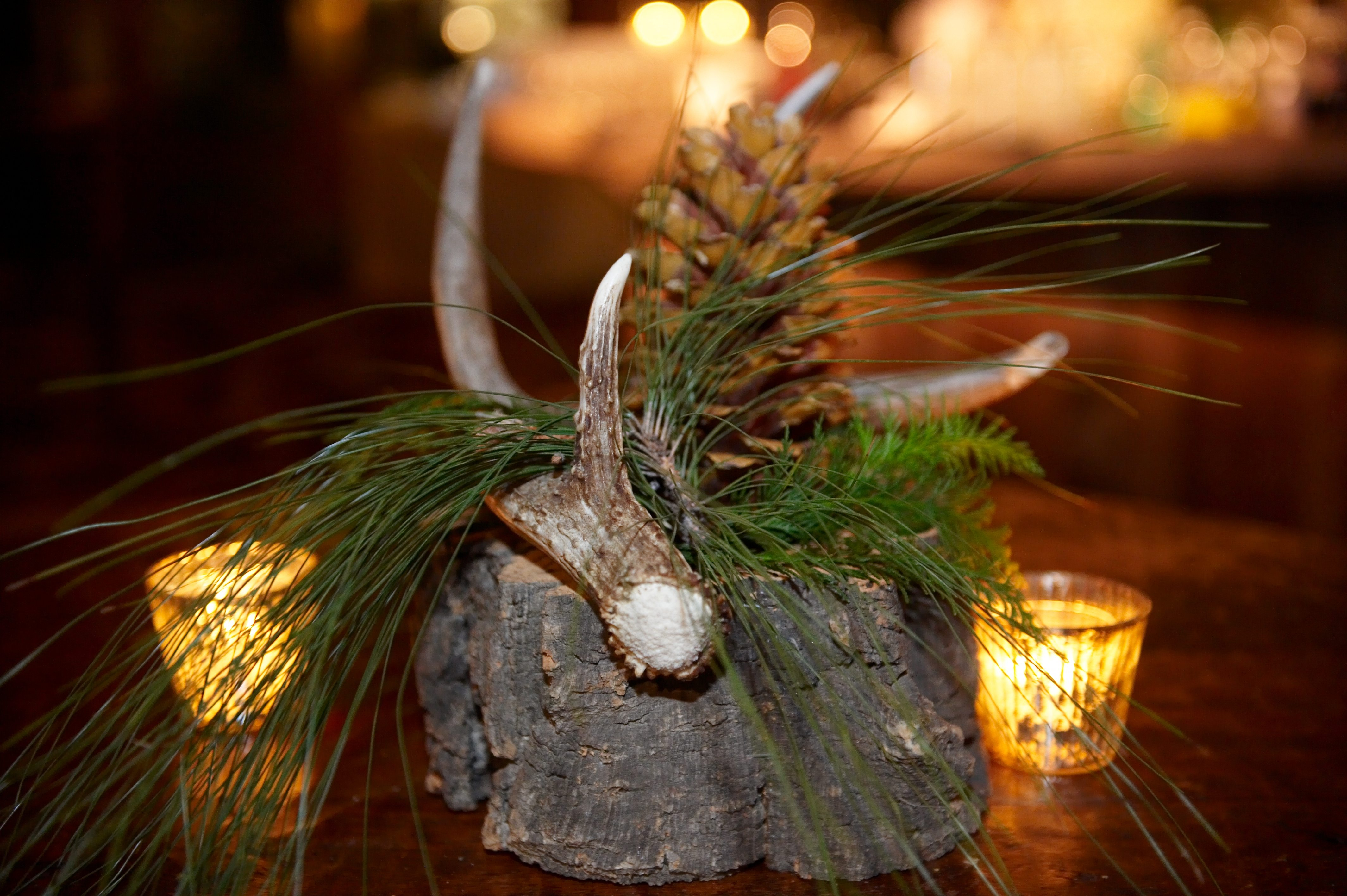 rustic wedding decor with large piece of tree trunk branch with antler and pine cone on top for centerpiece