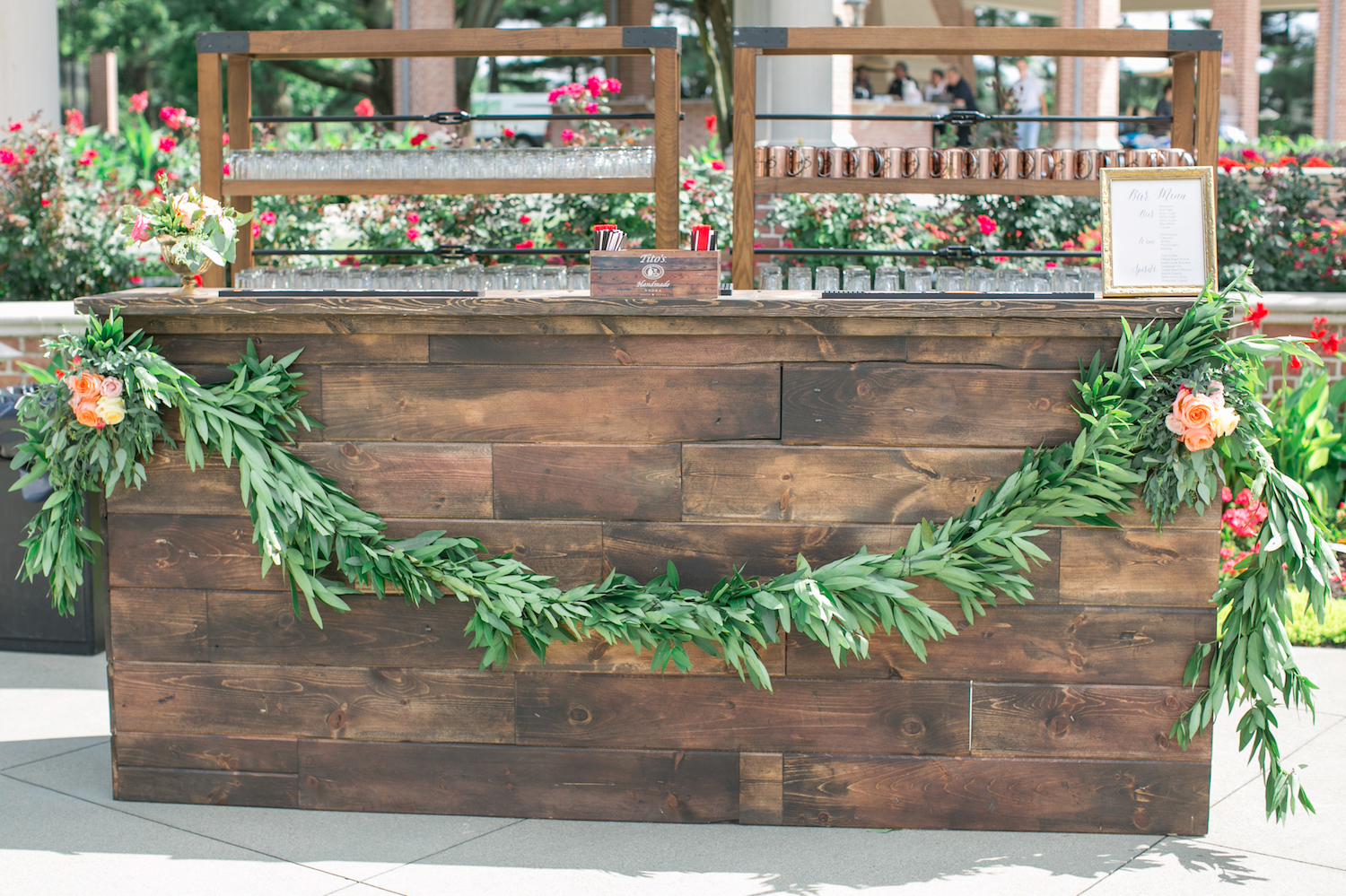 wedding reception with large wooden bar with garland of greenery across the front