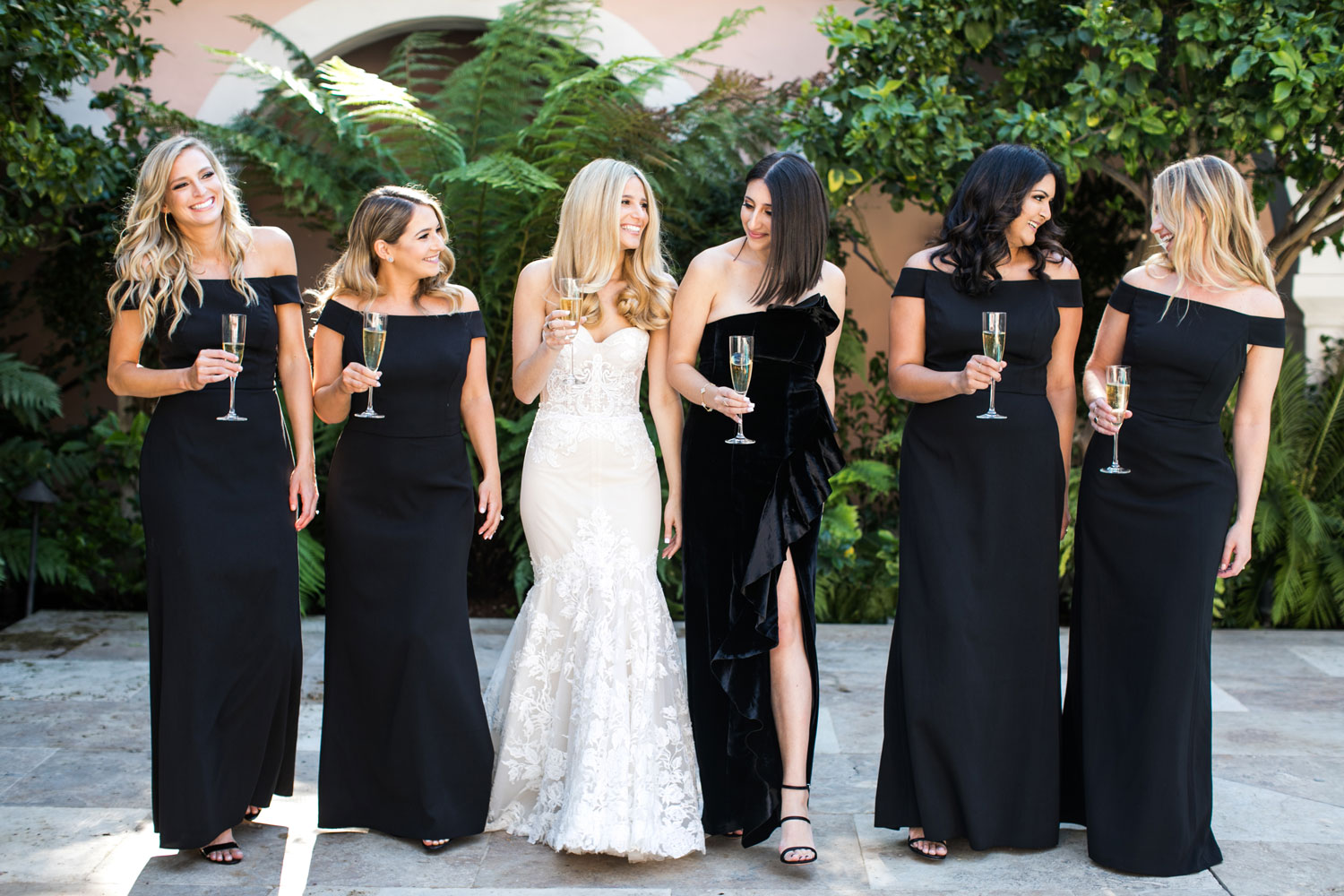 bride and bridesmaids with champagne, bridesmaids in off-the-shoulder black gown, maid of honor in black velvet dress, how to choose your bridal party