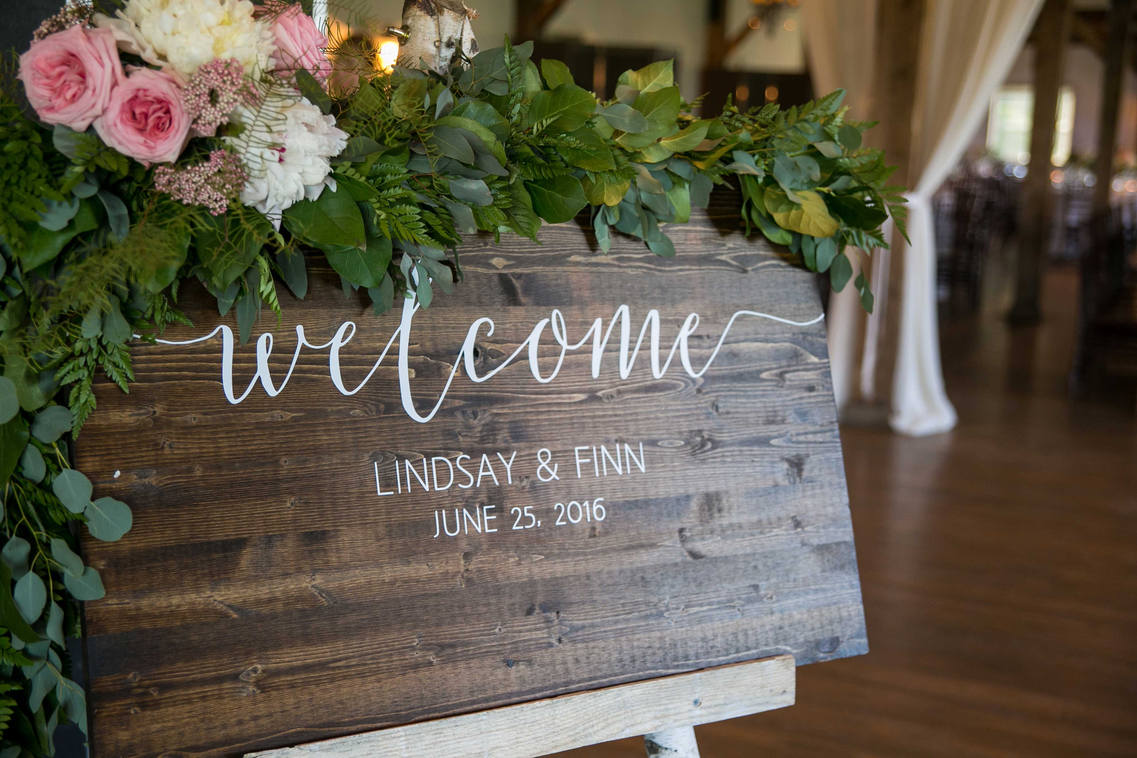 wooden welcome welcome sign with dark stain, white calligraphy, and fresh flowers on top