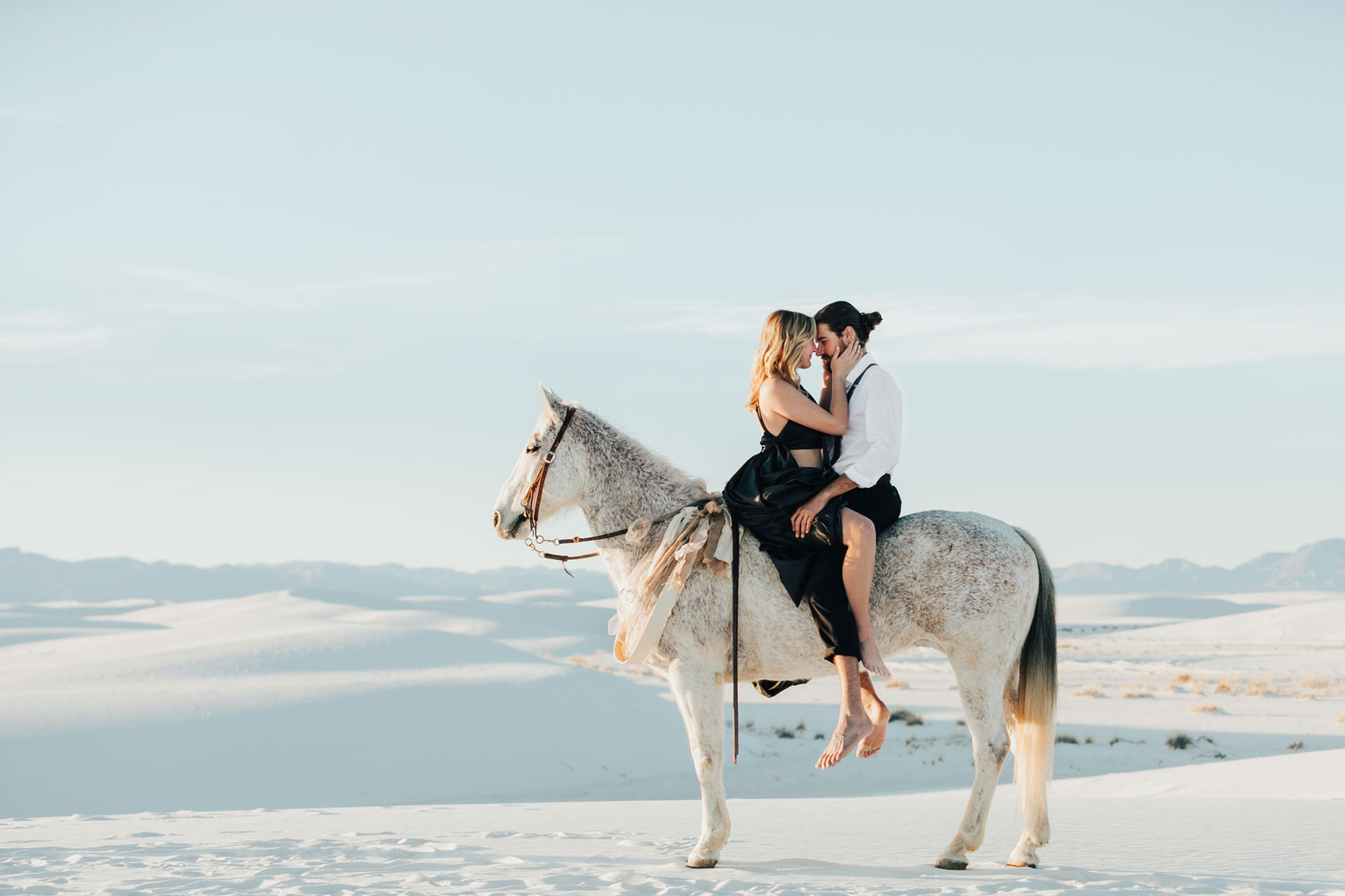 engagement photo shoot at White Sands National Monument in New Mexico engagement photos couple barefoot on horse
