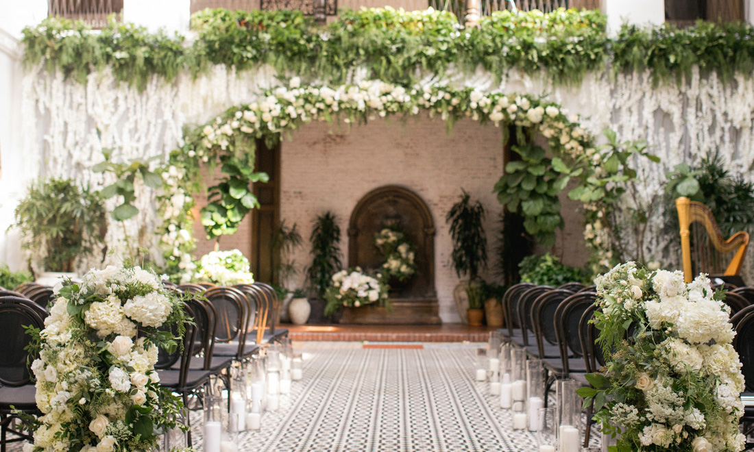 indoor wedding venue with balcony covered in lush florals, what to do when you arrive to a wedding too early