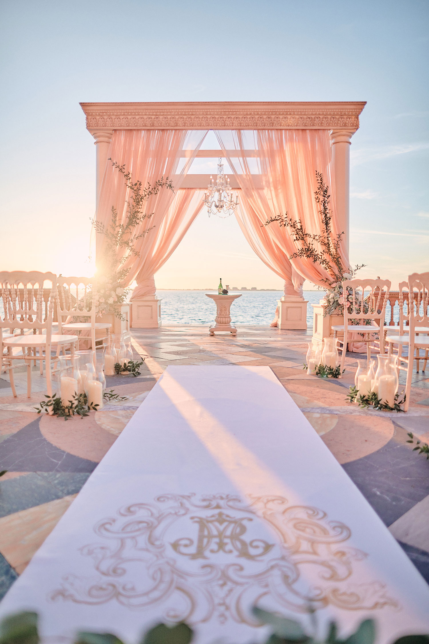 outdoor wedding ceremony sunset bay with personalized aisle runner