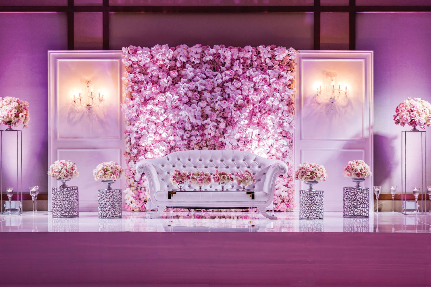 Inside Weddings magazine winter 2020 issue preview wedding reception stage with pink flowers and tufted sofa settee