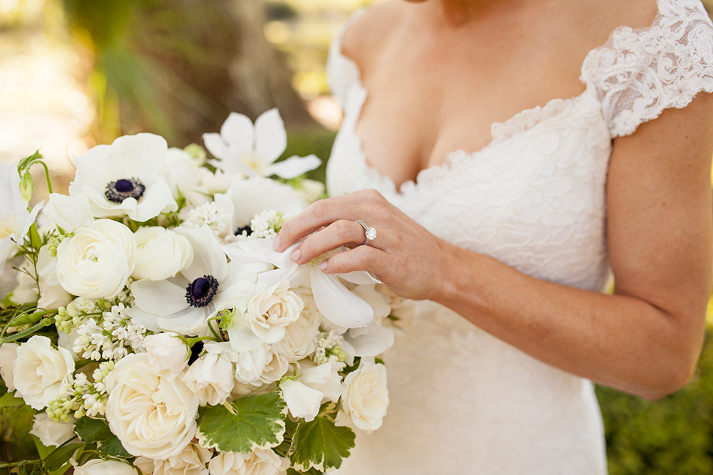 bride in lace wedding dress holding bouquet of anemone flowers and ivory blooms