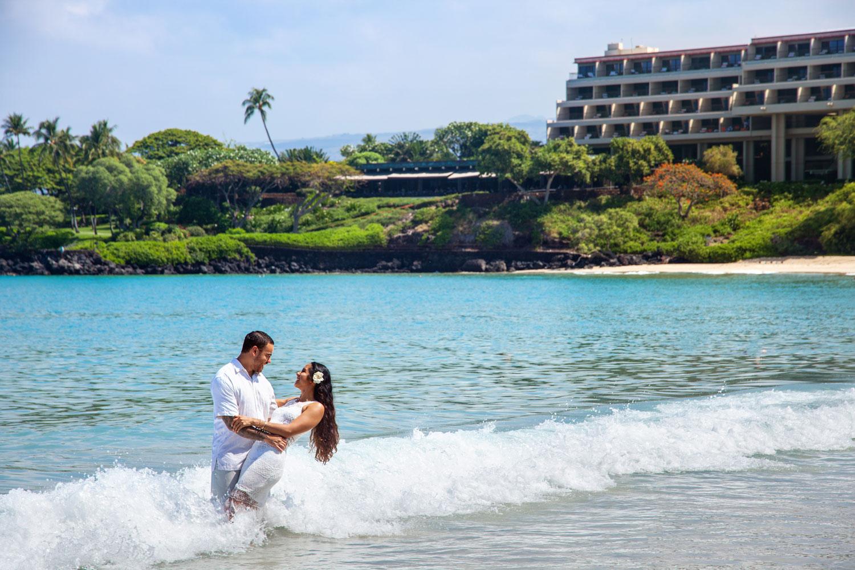 bride and groom in ocean at mauna kea beach hotel big island hawaii honeymoon wedding ideas