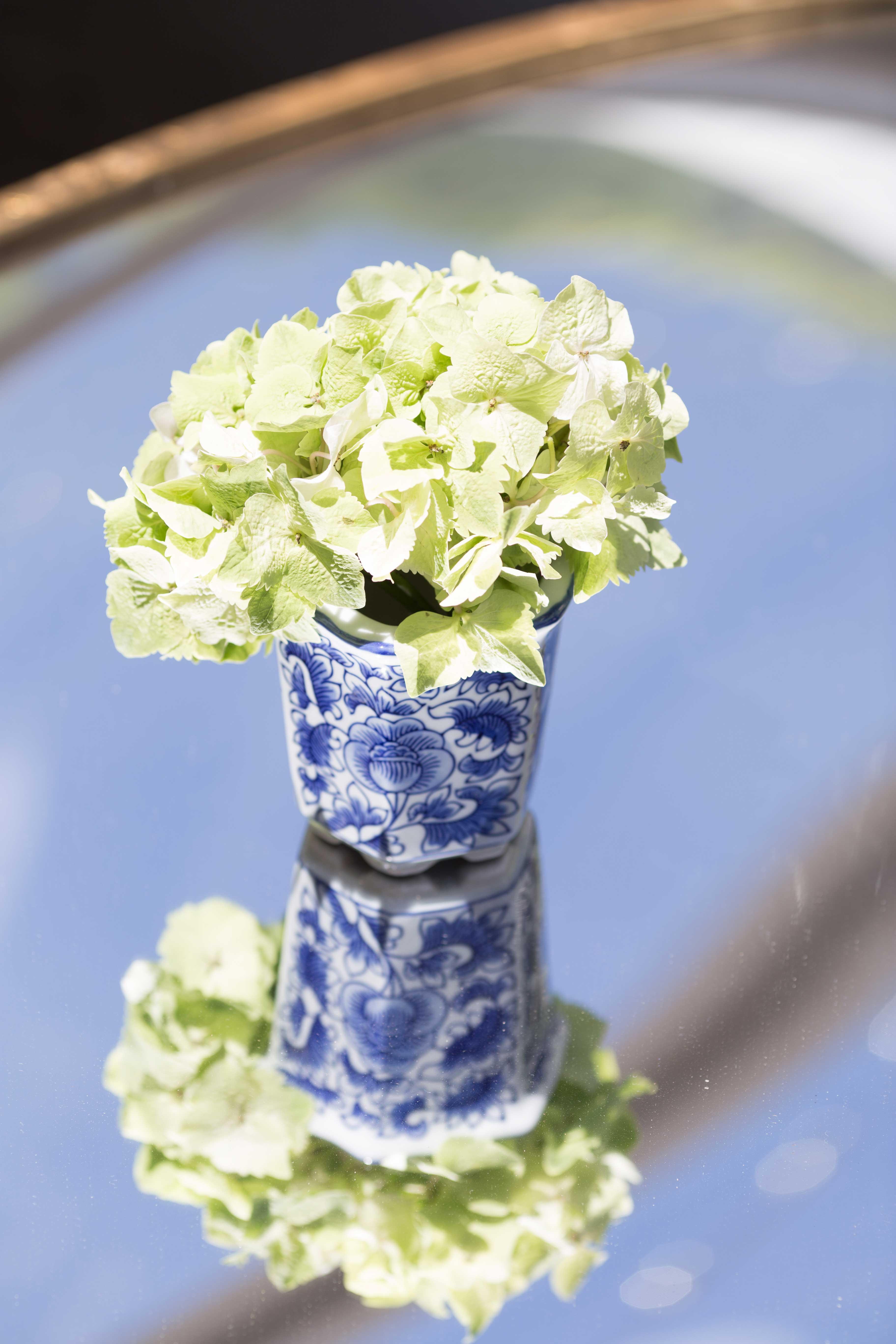 blue and white ginger jar on mirror table at wedding reception