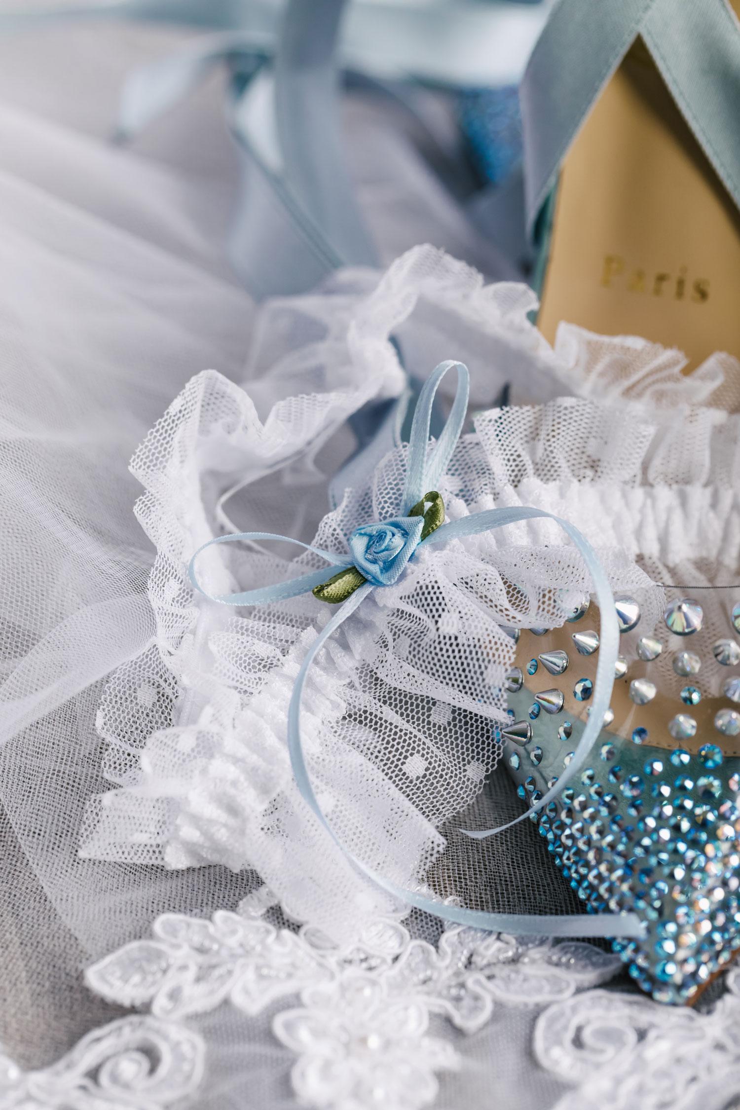 close up of wedding garter on top of something blue shoes wedding detail shot
