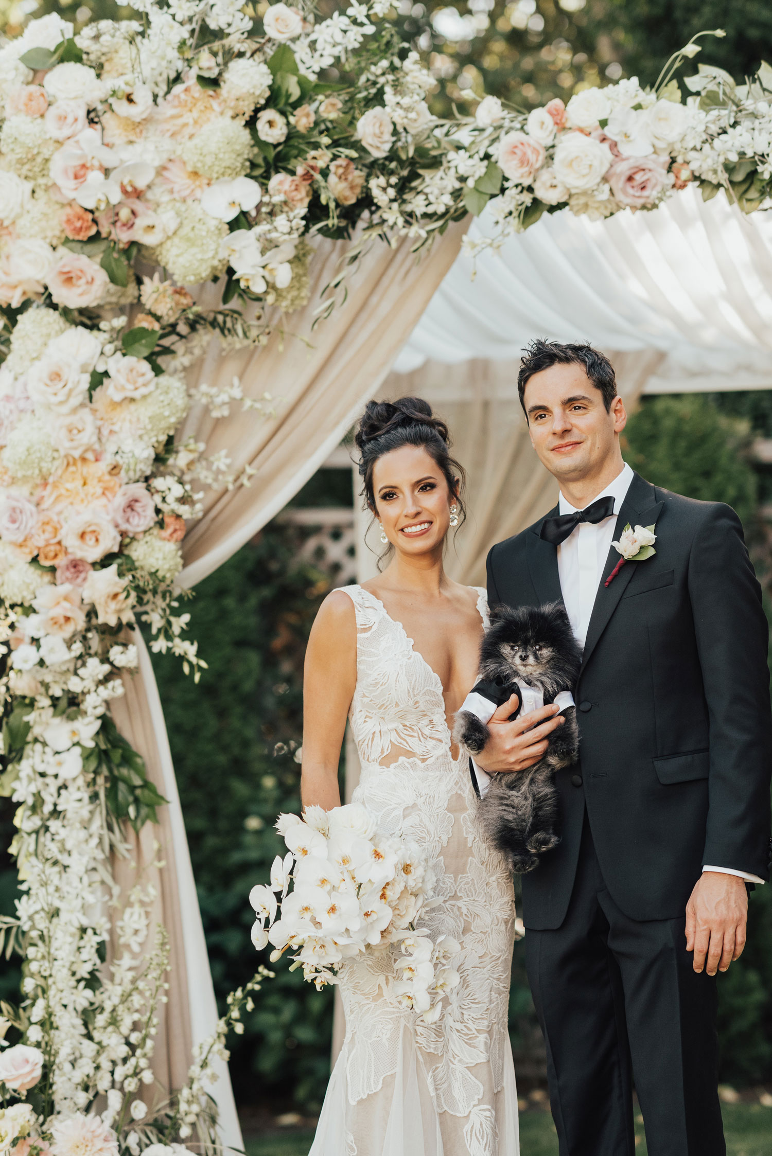 bride and groom with pomeranian dog puppy in mini tuxedo protea wedding bouquet