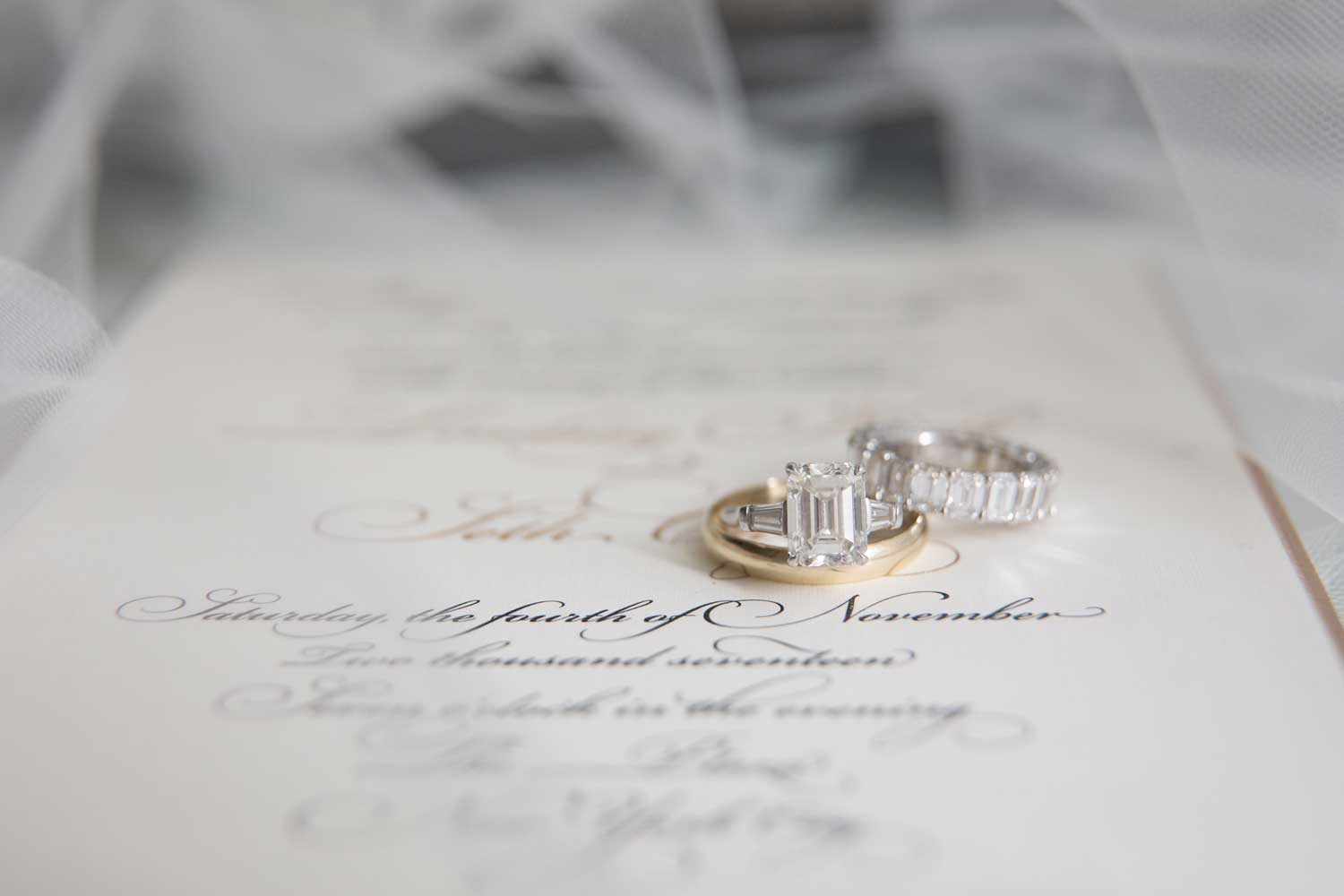 close up of engagement ring and wedding rings on invitation detail shot for your wedding album