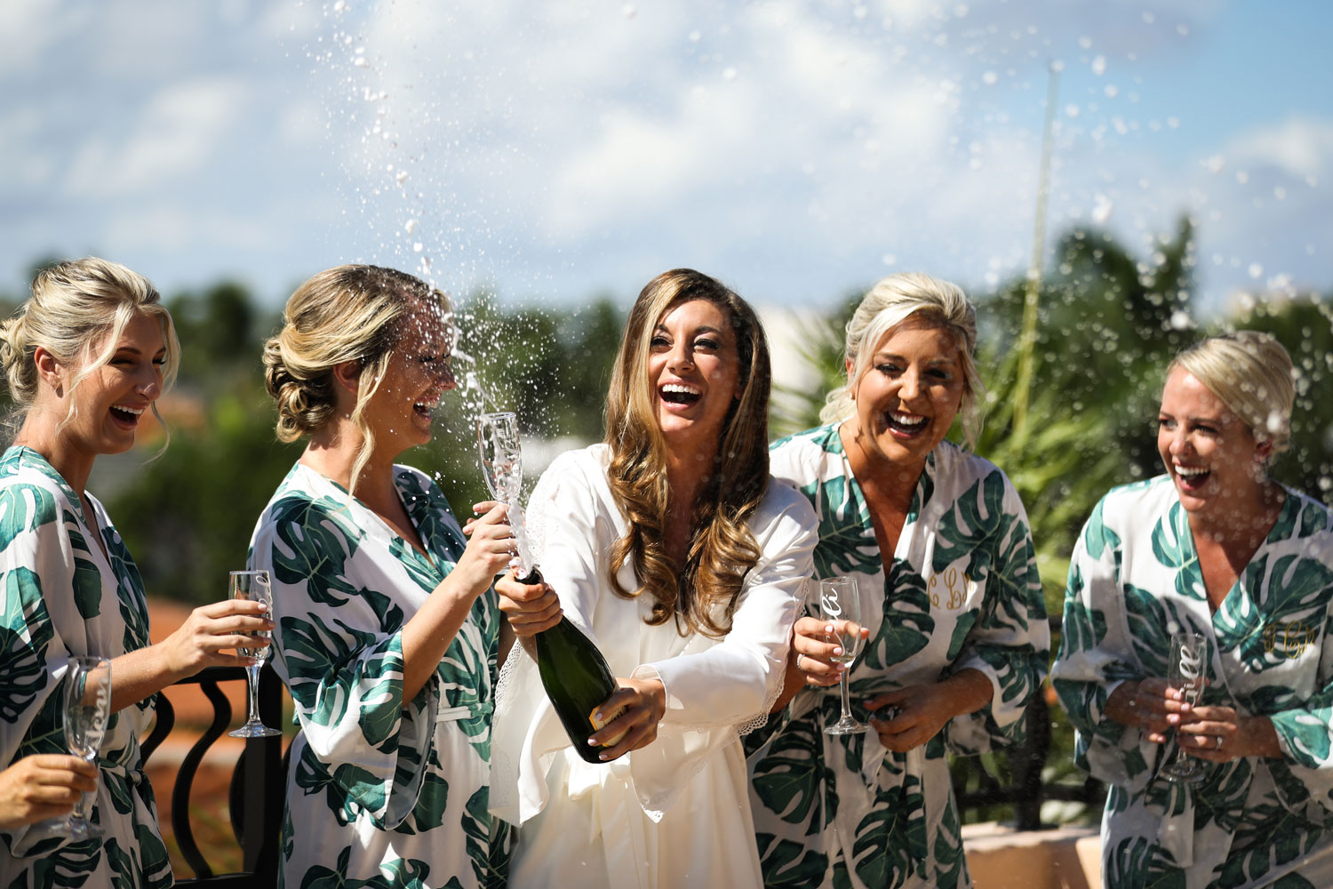 bride with bridesmaids in robes popping champagne in celebration